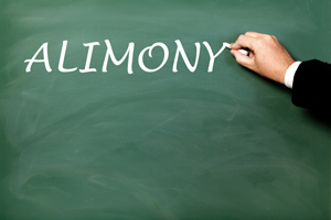 A hand writing alimony in white chalk on a chalk board